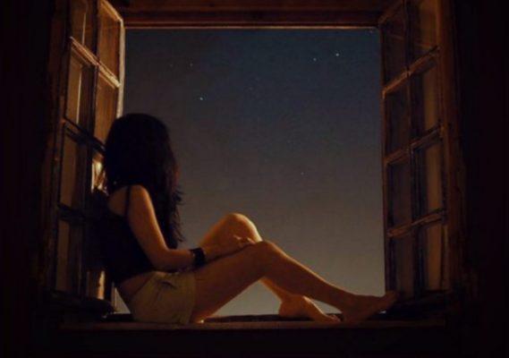 дівчина дивиться у відкрите вікно